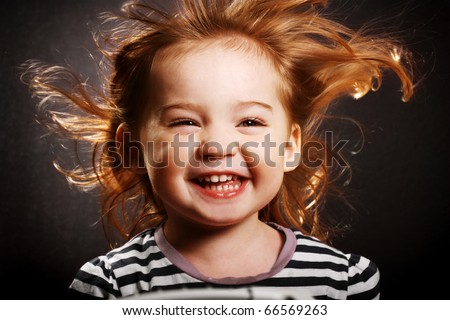 A gorgeous little girl smiling hysterically with the wind in her hair. - stock photo