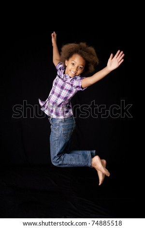 A gorgeous little 7yr old African girl in the studio. Black background. - stock photo