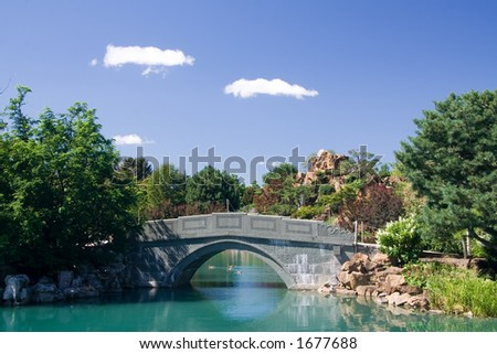 A gorgeous stone bridge crosses the pond of the Chinese garden at the Montreal Botanical Gardens. - stock photo