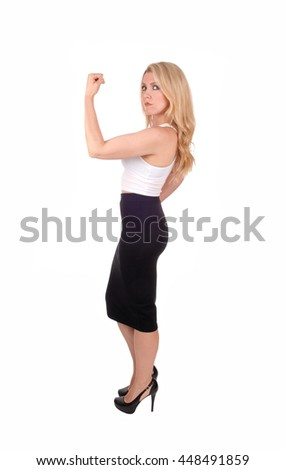 A gorgeous young blond woman standing in a black skirt and white blouse in profile, isolated for white background. - stock photo