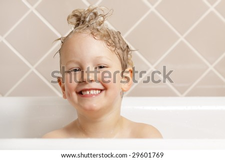 A gorgeous young boy has fun in the bath. - stock photo