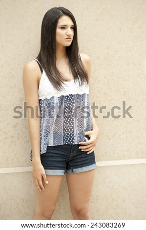 A gorgeous young brunette girl posing on a light brown background outdoors on a sunny day. - stock photo
