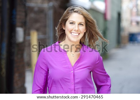 A gorgeous young female model wearing a pink shirt on a sunny day. - stock photo