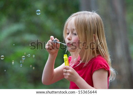 A gorgeous young girl blowing soap bubbles in a natural outdoor setting.