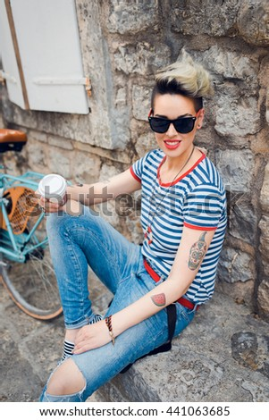 A gorgeous young woman enjoying some coffee while resting near her bicycle - stock photo