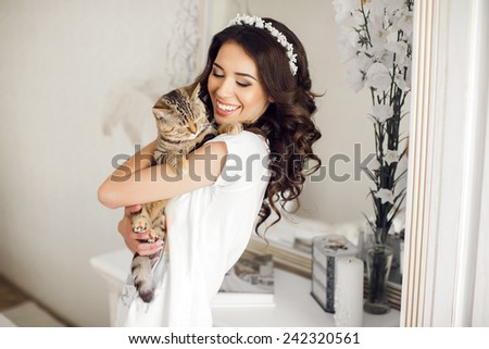 A gorgeous young woman with a cat on hands. close-up portrait of a beautiful girl holding british cat. Portrait of a beautiful girl at home - stock photo