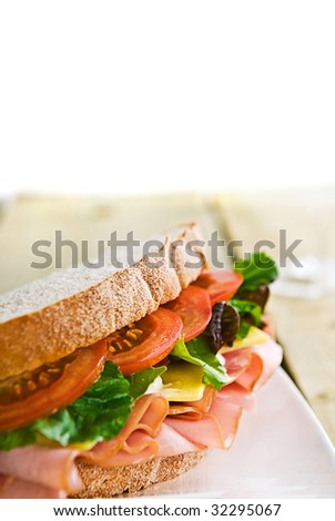 A gourmet sandwich of ham, cheese, lettuce, tomato and mayonnaise isolated on white. - stock photo