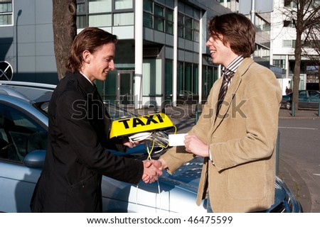 A government official handing a taxi license and sign to a newly appointed taxi driver whilst shaking his hand - stock photo