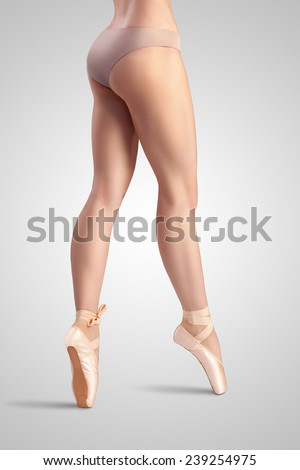 A graceful female classical ballet dancer on pointe shoes wearing beige satin underwear and standing on toes on a neutral light studio background. - stock photo