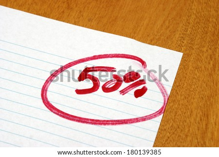 A graded exame paper with a fifty per cent mark. - stock photo