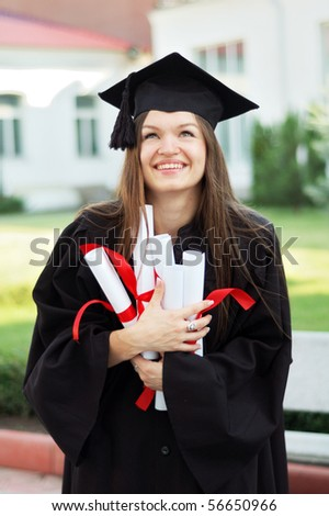 A graduate in the mantle holds many diplomas and looks up - stock photo