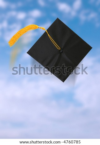 A graduation cap after being thrown into the blue sky - stock photo