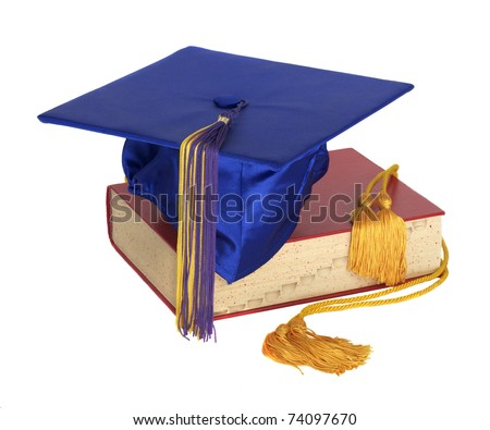 A graduation hat and honor cord on top of a text book - stock photo