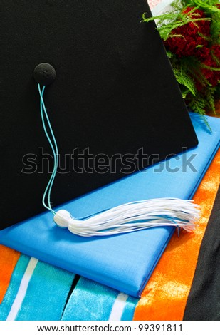 A graduation set with bouquet,cap,tassel, gown, hood and diploma. - stock photo