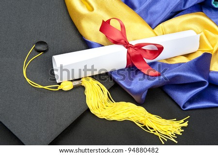 A graduation setting with cap,tassel, gown, hood and diploma. - stock photo