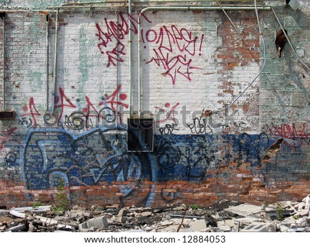 A graffiti covered wall of an abandoned brick building, which is painted white and blue. - stock photo