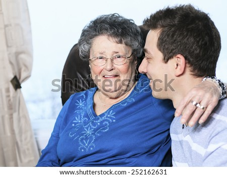 A grandchild with his grandmother in his room - stock photo
