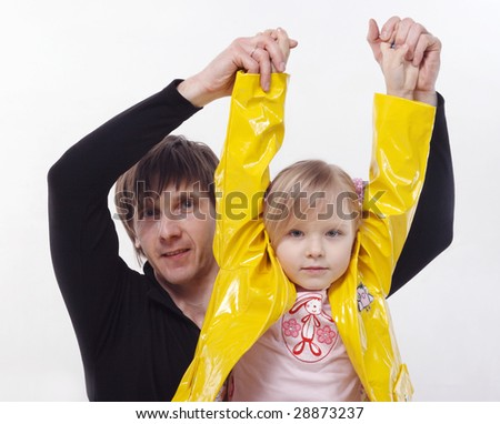 A granddad holds a little grandchild on hands on a grey background - stock photo