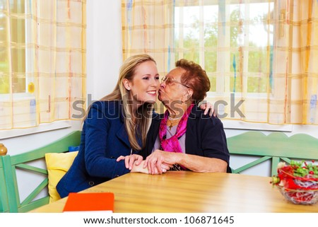 a granddaughter to visit his grandmother. hugs and kisses - stock photo