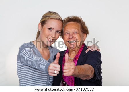 a granddaughter visits her grandmother. laughter and joy. thumbs up - stock photo