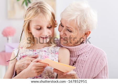 A grandma with a birthday card from her granddaughter - stock photo