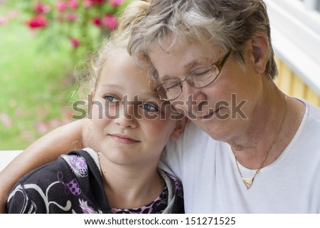 a grandmother and grandchild looking at camera, candid photo, real people - stock photo