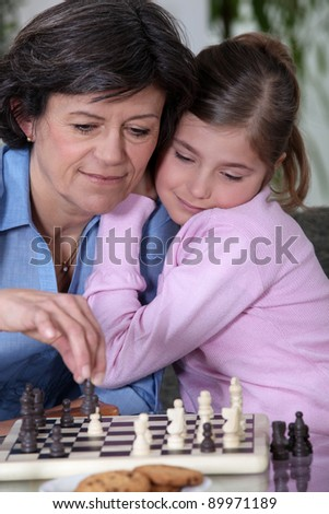 A grandmother and her granddaughter playing chess. - stock photo