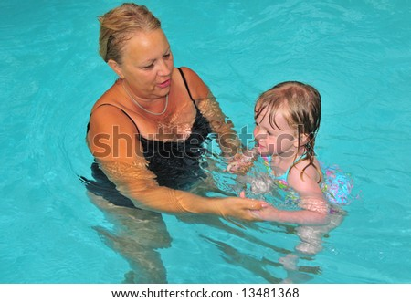 A grandmother and her granddaughter work on their swimming in the pool - stock photo