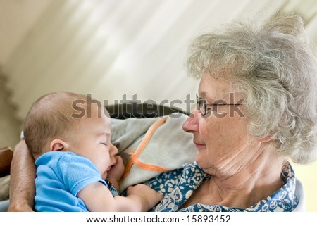 a grandmother holding a new little grandson - stock photo