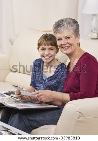 A grandmother is seated on a couch with her granddaughter and they are looking through a wedding album.  They are smiling at the camera.  Vertically framed shot. - stock photo
