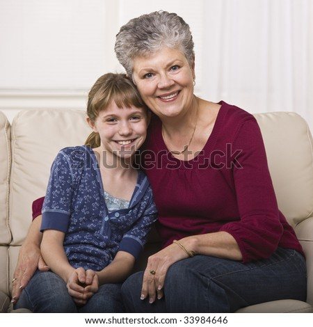 A grandmother is sitting on a couch and hugging her granddaughter.  They are smiling at the camera.  Square framed shot. - stock photo