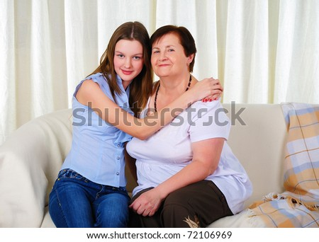 a grandmother with her young granddaughter together sitting on a sofa - stock photo