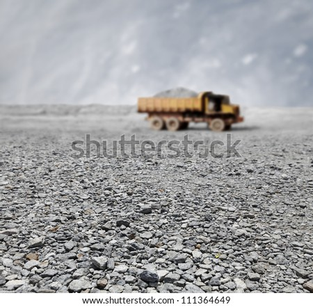 A granite quarry mine with a tipper lorry transporting stones in the horizon. - stock photo