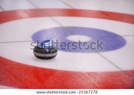 A granite 'rock' lands in the target in a game of Curling. The pebbled ice is a part of the rink preparation.