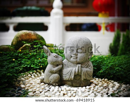 A granite statue of a cute little monk with a rabbit which is the fourth zodiac sign in the Chinese horoscope in a buddhist temple garden. - stock photo