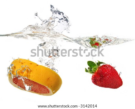 a grapefruit and a strawberry are falling in water with a big splash - stock photo