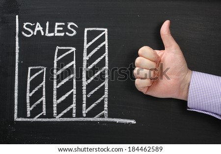 A graph showing Sales rising on a blackboard with a hand in a business shirt giving the okay thumbs up - stock photo