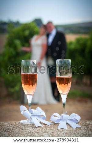 a graphic abstract of wine glasses focused against a blurred background of a couple standing outside who have just got married  - stock photo