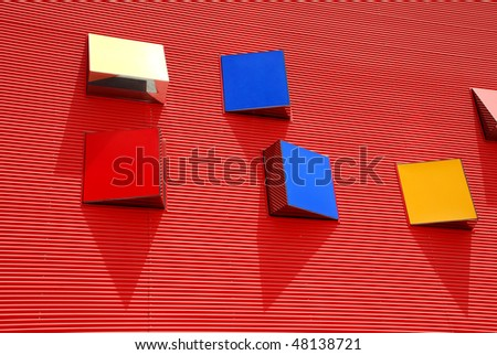A graphic look of colorful windows on a bright red wall - stock photo