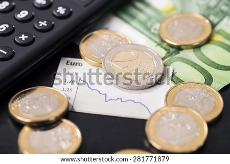A graphic shows the falling euro rate and is surrounded by euro coins. - stock photo