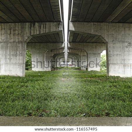 A grass patch underneath a colossal elevated concrete highway. - stock photo