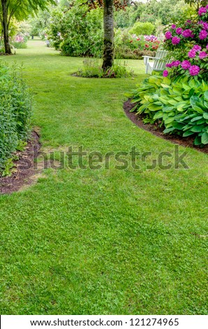 A grass walkway leads through a blooming garden - stock photo