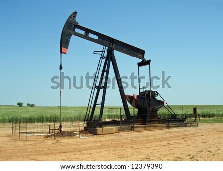 A grasshopper pump pumps oil in the midst of a wheat field - stock photo