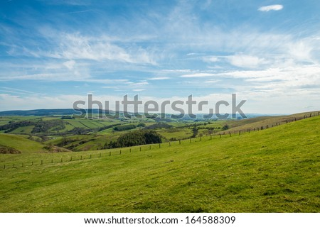 A grassy field overlooking the Welsh countryside. - stock photo