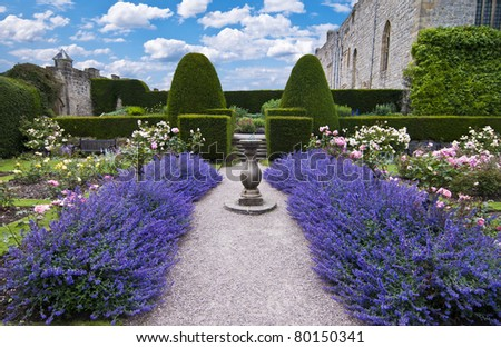 a gravel pathway between formal beds of lavender leading to an old sundial and trimmed hedges beyond. Horizontal format. - stock photo