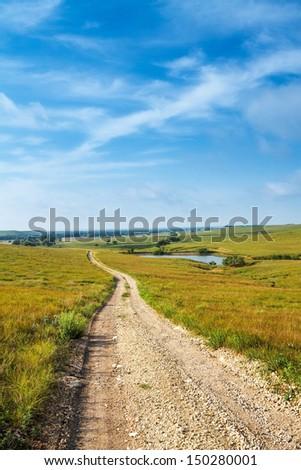 A gravel road going through a grass prairie in the flint hills of Kansas. - stock photo