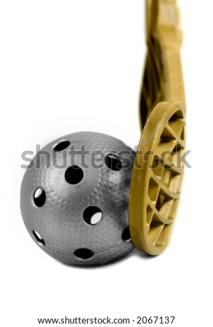 A gray floorball ball and a golden stick. - stock photo