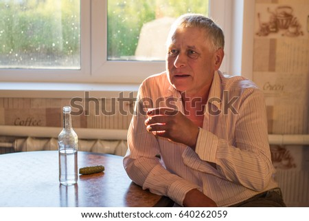 A gray-haired gray man is sitting at the kitchen table, on which stands a bottle of alcohol, a pickled cucumber, and holds a glass of vodka in his hand. Social problems: alcoholism