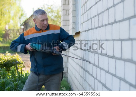 A gray-haired man drills a white brick wall at home with a perforator