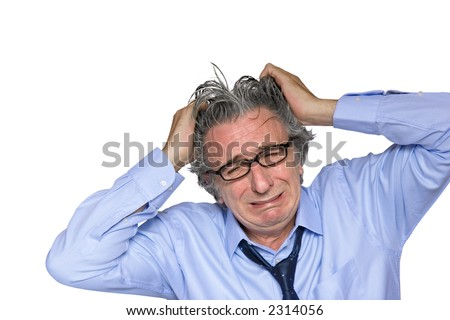 A gray-haired senior with glasses wearing a light blue shirt is crying. - stock photo